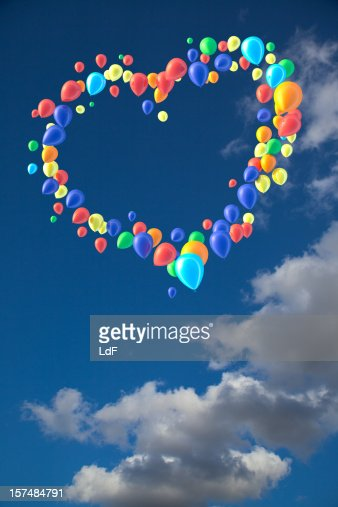 Heart shape of balloons against sky with puffy clouds : Stock Photo
