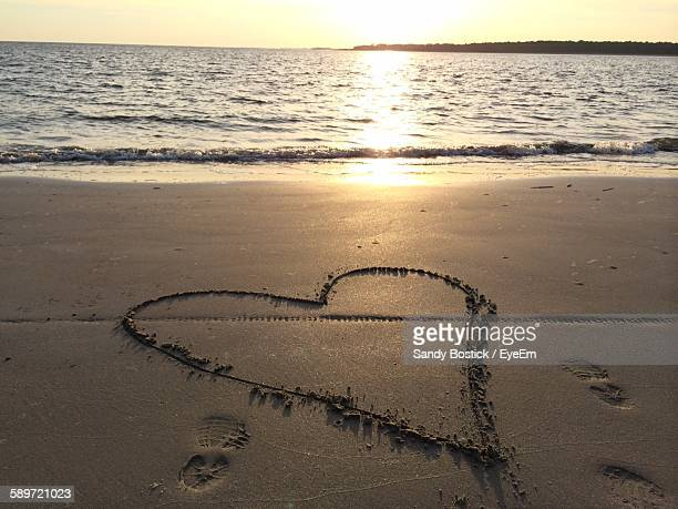 Heart Shape On Sand At Beach During Sunset