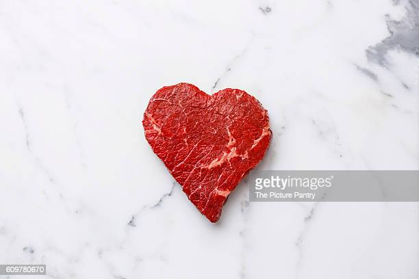 Heart shape Raw fresh meat on white marble background