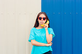 Cute confused girl talking on banana telephone