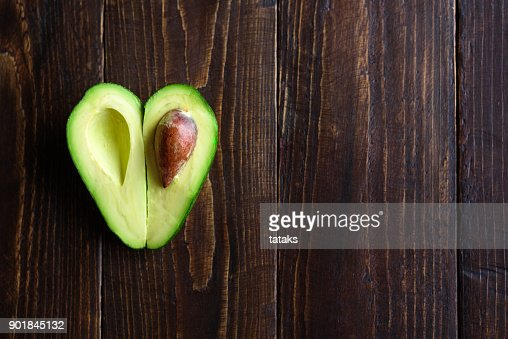 Heart shaped avocado on wooden background : Stock Photo