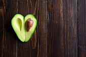 Heart shaped avocado half on wooden background