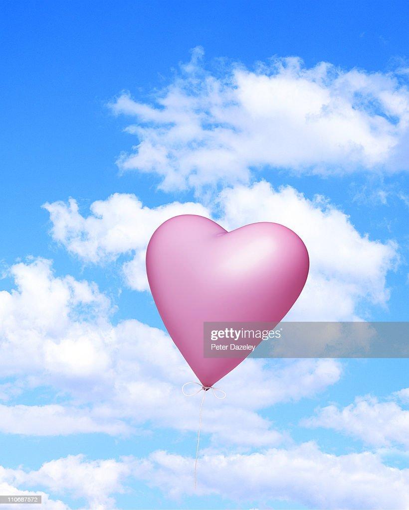 Heart shaped balloon against sky : Stock Photo