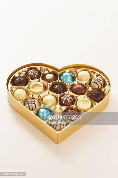 Heart shaped box of chocolates on white background