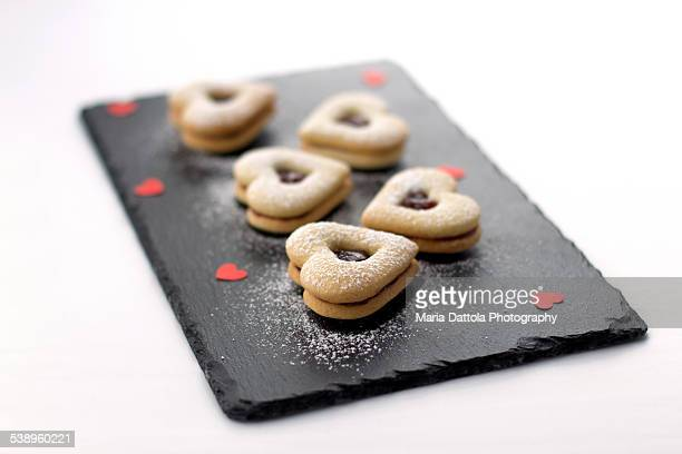 Heart shaped cookie with jam on a slate plate