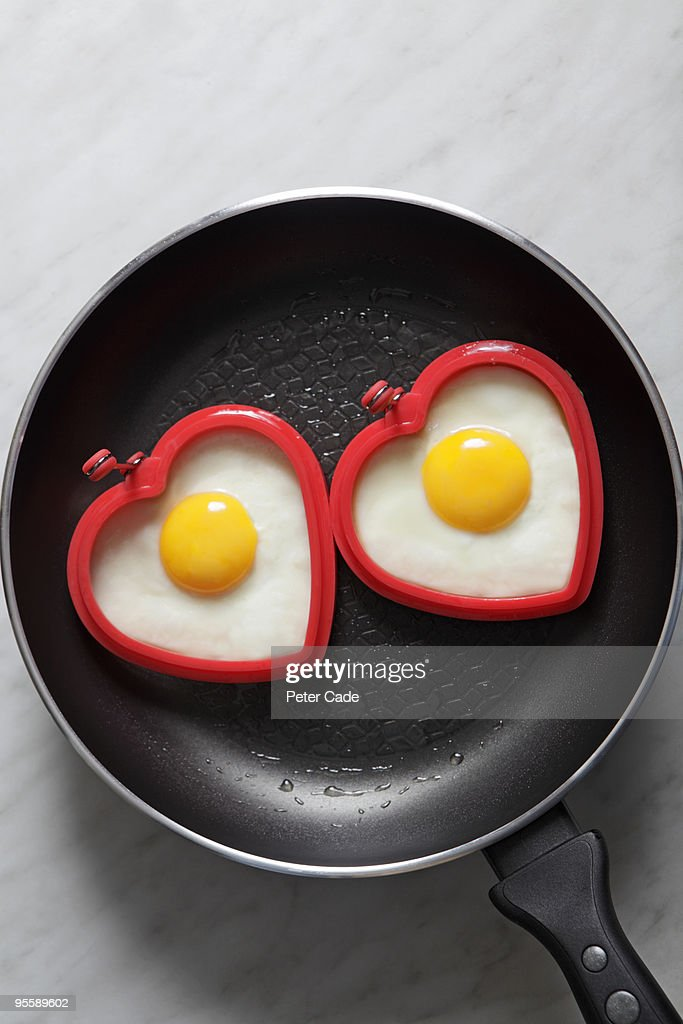 heart shaped eggs in pan : Stock Photo