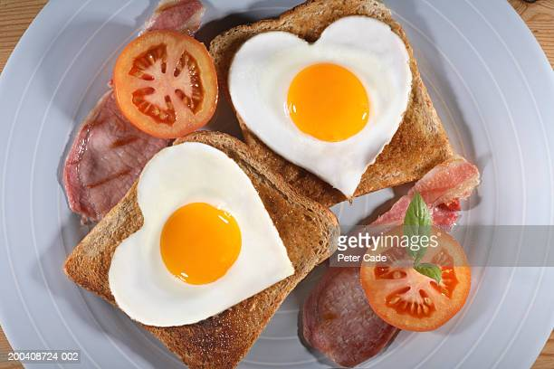 Heart shaped eggs on toast with bacon and tomatoes, overhead view
