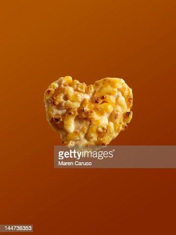 Heart shaped macaroni and cheese on orange : Stock Photo