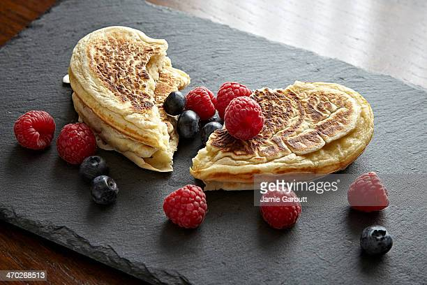 Heart shaped pancakes torn in two with fresh fruit