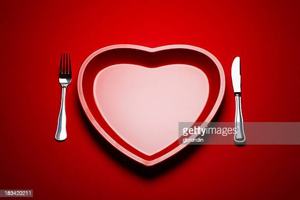 Heart shaped plastic plate on red background