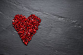 Heart shaped pile of pomegranate seeds on dark grey background. Top view point.