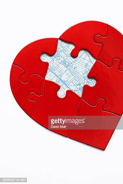 Heart shaped puzzel with piece missing, with map underneath