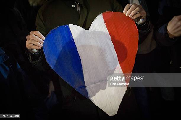 A heart shaped sign with the colors of the French flag is held as people hold a vigil for victims of the Paris terrorist attacks in Trafalgar Square...