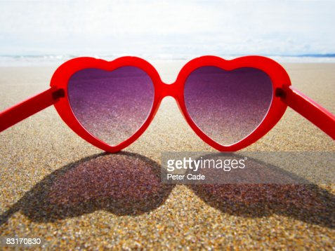 heart shaped sunglasses on beach : Stock Photo