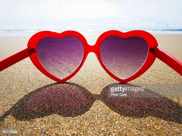 heart shaped sunglasses on beach
