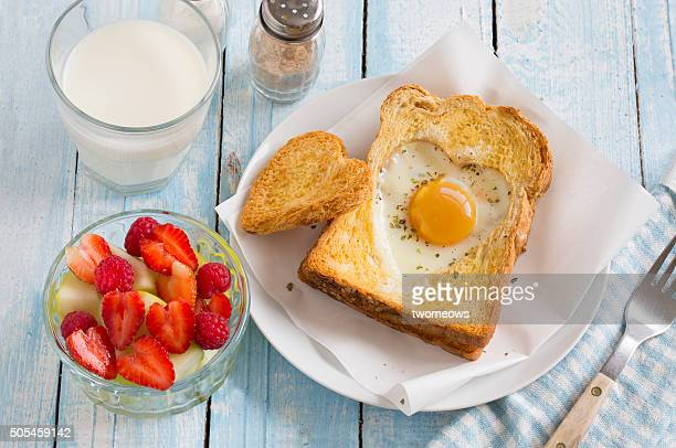 Heart shaped sunny side egg with toast on wooden background.