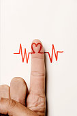 a red heart symbol in the forefinger of a man as in an electrocardiogram painted on an off-white background, with a blank space on top