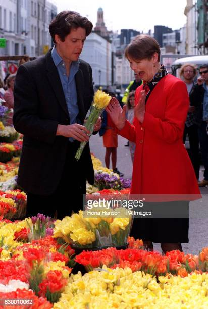 Heart throb actor Hugh Grant presents a surprised actress turned London Transport minister Glenda Jackson with a bunch of flowers during her visit to...