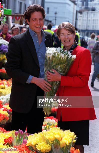 Heart throb actor Hugh Grant presents actress turned London Transport minister Glenda Jackson with a bunch of flowers during her visit to the set of...
