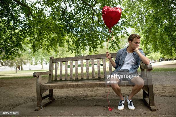 Heartbroken man at the park holding a heart shaped balloon