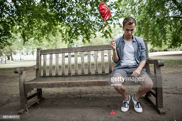 Heartbroken man at the park looking very sad
