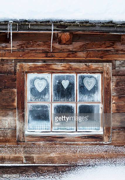 Hearts on window of log cabin, Austrian Alps, Austria