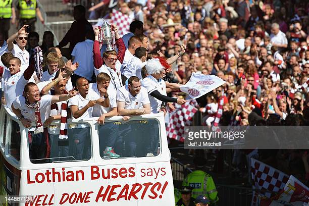 Hearts players parade along Gorgie Road on an open top bus following following their Scottish Cup final win over rivals Hibernian on May 20 2012 in...
