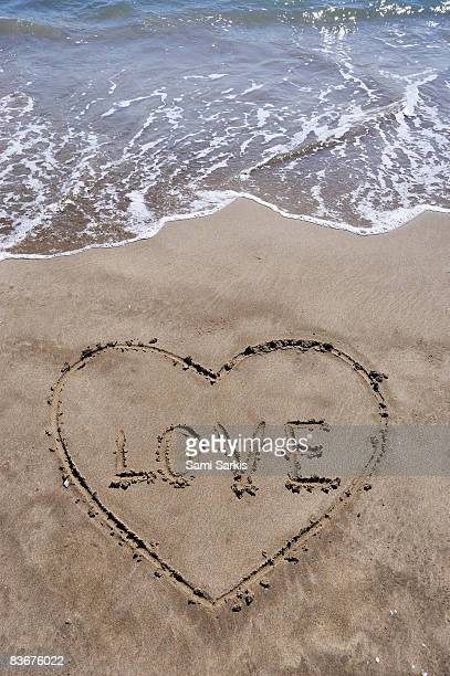 Heartshape drawn in sand on beach