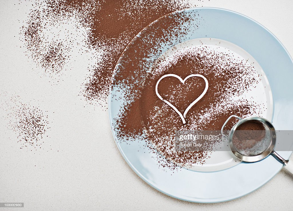Heart-shape drawn into cocoa powder on plate