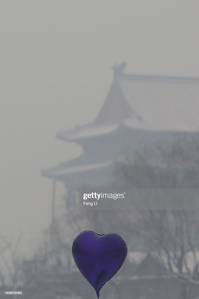 A heart-shaped balloon is seen in front of Drum Tower at Houhai Lake during severe pollution on February 3, 2013 in Beijing, China. Houhai Lake is a popular place for winter sport and entertainment in Beijing.