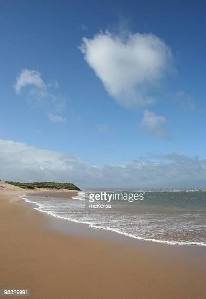 Herzförmige Wolke über sandigen Strand mit Wellen