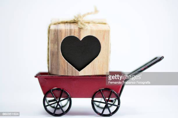 Heart-shaped gift inside a wheelbarrow. Valentine´s day