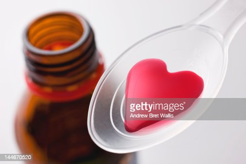 Heart-shaped liquid medicine on a spoon : Stock Photo