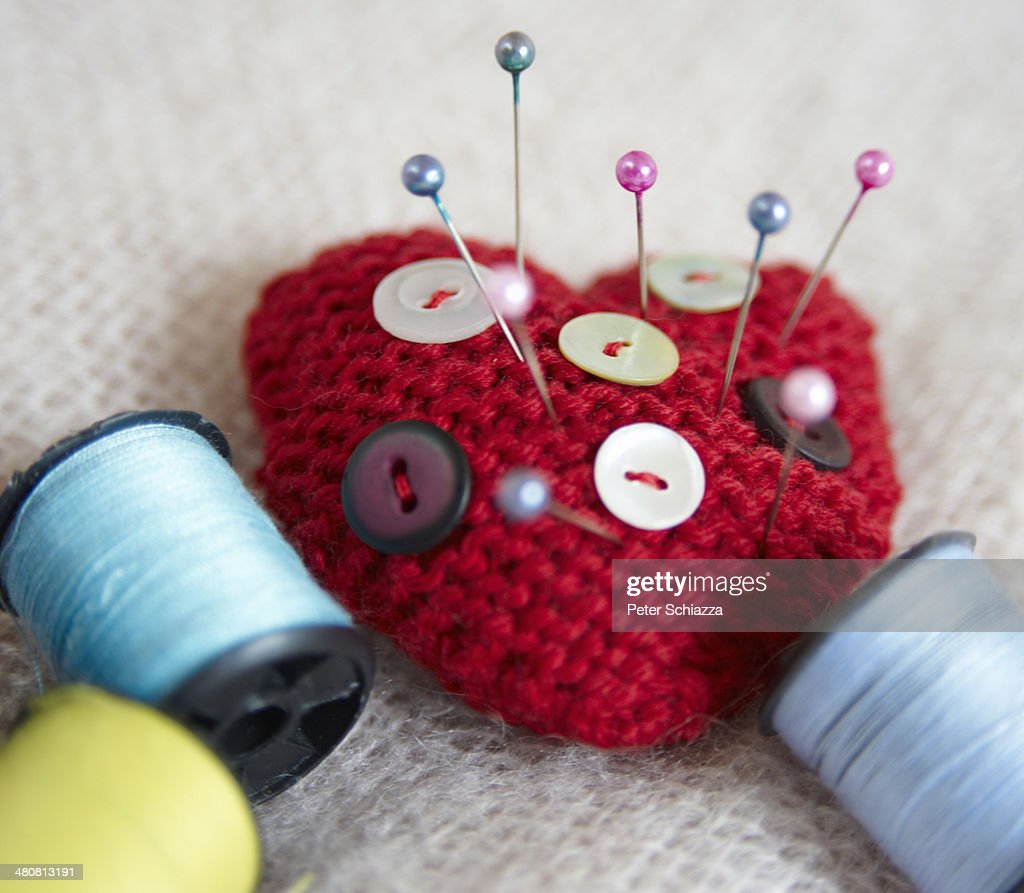 Heart-shaped pin cushion. buttons and thread