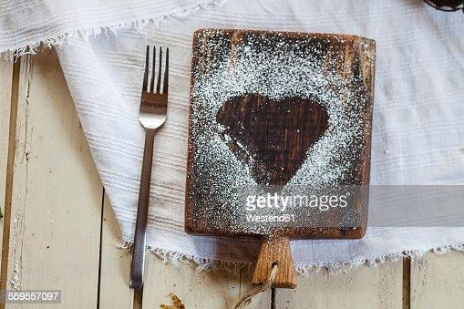 Heart-shaped powdered sugar on cutting board
