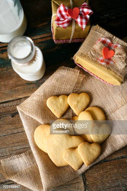 Heart-shaped shortbreads on jute, glass bottle of milk and two gift boxes