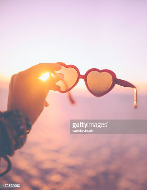 Heart-shaped sunglasses being held with a sunset behind