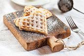 Heart-shaped waffles on cutting board
