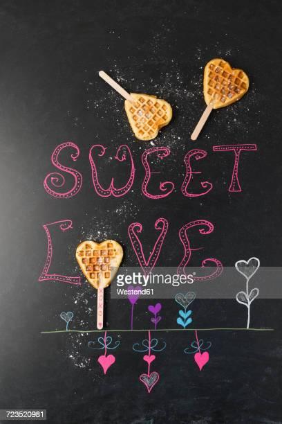Heart-shaped waffles on painted blackboard
