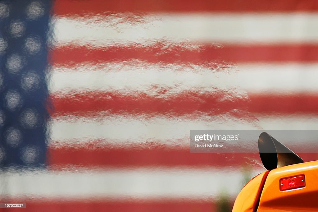 Heat waves emanate from the exhaust pipe of a city transit bus as it passes an American flag hung on the Los Angeles County Hall of Justice by...