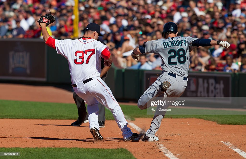 Heath Hembree #37 of the Boston Red Sox covers first base for the out on Chris Denorfia #28 of the Seattle Mariners during the sixth inning at Fenway Park on August 24, 2014 in Boston, Massachusetts.