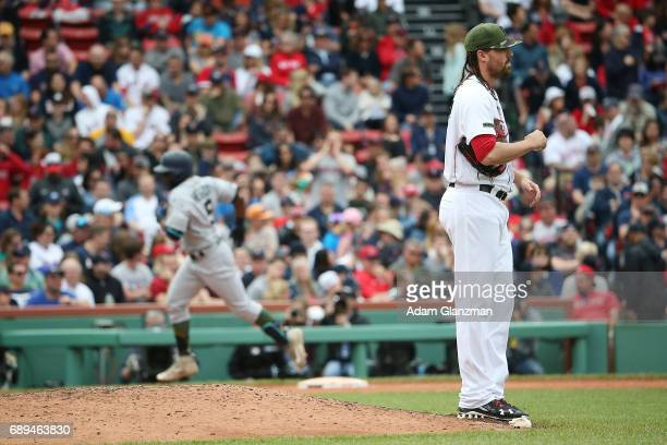 Heath Hembree of the Boston Red Sox looks on as Guillermo Heredia of the Seattle Mariners rounds the bases after hitting a solo home run in the...