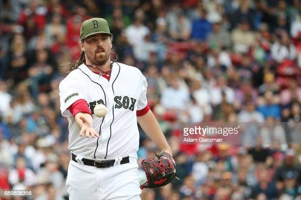 Heath Hembree of the Boston Red Sox tosses the ball to first base in the eighth inning of a game against the Seattle Mariners at Fenway Park on May...