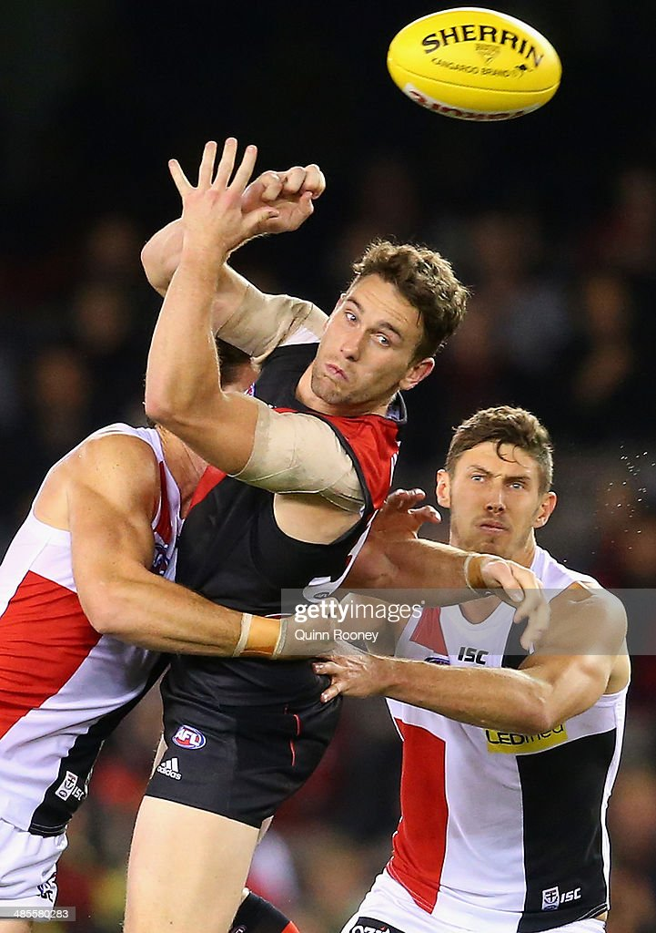 Heath Hocking of the Bombers handballs whilst being tackled by <a gi-track='captionPersonalityLinkClicked' href=/galleries/search?phrase=Lenny+Hayes&family=editorial&specificpeople=208719 ng-click='$event.stopPropagation()'>Lenny Hayes</a> of the Saints during the round five AFL match between the Essendon Bombers and the St Kilda Saints at Etihad Stadium on April 19, 2014 in Melbourne, Australia.