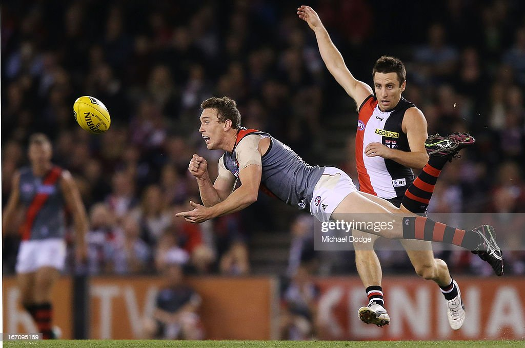 Heath Hocking of the Bombers handpasses the ball away from <a gi-track='captionPersonalityLinkClicked' href=/galleries/search?phrase=Stephen+Milne&family=editorial&specificpeople=171906 ng-click='$event.stopPropagation()'>Stephen Milne</a> of the Saints during the round four AFL match between the St Kilda Saints and the Essendon Bombers at Etihad Stadium on April 20, 2013 in Melbourne, Australia.