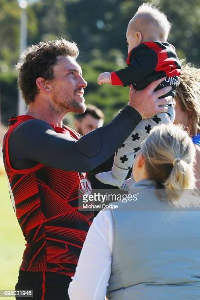 Heath Hocking of the Bombers holds up a fas baby during an Essendon Bombers AFL training session at True Value Centre on June 20 2017 in Melbourne...