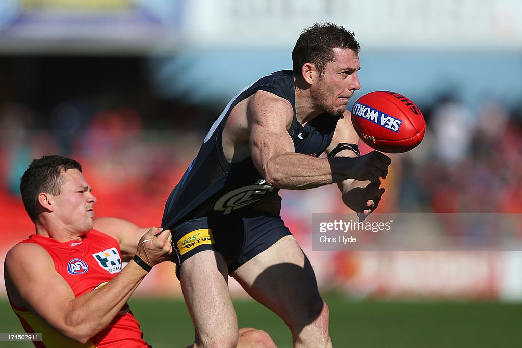 Heath Scotland of the Blues handballs while tackled by Steven May of the Suns during the round 18 AFL match between the Gold Coast Suns and the Carlton Blues at Metricon Stadium on July 27, 2013 in Gold Coast, Australia.