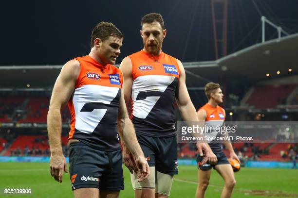 Heath Shaw of the Giants talks to team mate Shane Mumford as they leave the field following the round 15 AFL match between the Greater Western Sydney...