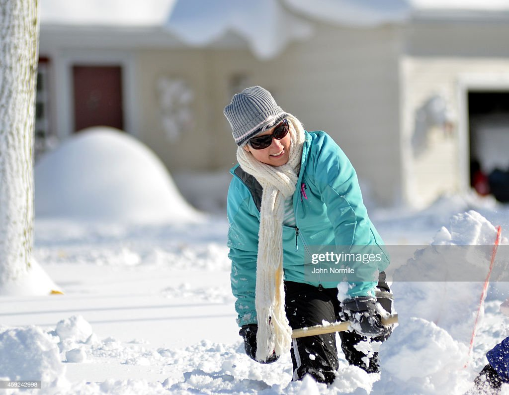 Heather Ahmed shovels her way through nearly five feet of snow on November 19 2014 in the Lakeview neighborhood of Buffalo New York The record...