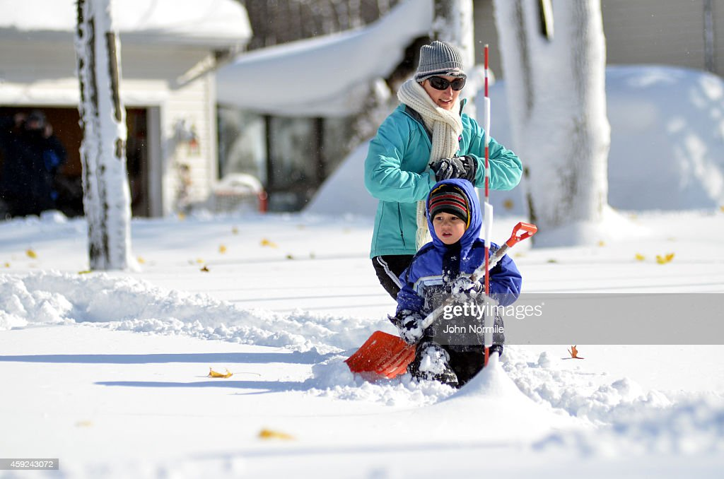 Heather and Braden Ahmed makes their way through nearly five feet of snow on November 19 2014 in the Lakeview neighborhood of Buffalo New York The...